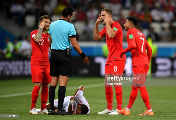 England players Kieran Trippier Jordan Henderson and Jesse Lingard speak with Referee Wilmar Roldan as Ali Maaloul of Tunisia goes down during the...
