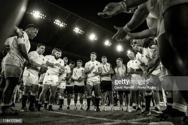 England players listen to Owen Farrell following their victory during the Rugby World Cup 2019 SemiFinal match between England and New Zealand at...
