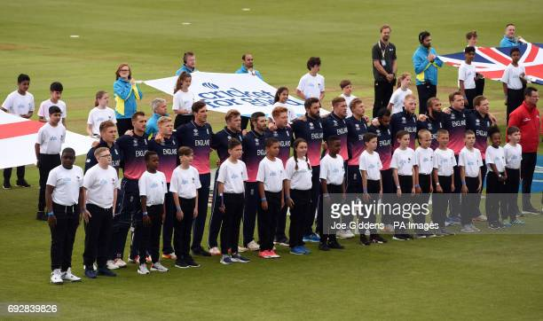 England players observe the national anthem during the ICC Champions Trophy Group A match at Cardiff Wales Stadium