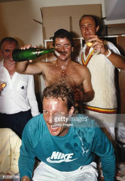 England players Phil Edmonds and Allan Lamb pour champagne over team mate Ian Botham in the dressing room during celebrations after England had...