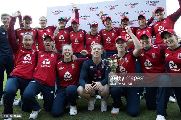 England players pose with the series trophy following their victory in the fifth women's Twenty20 cricket match between New Zealand and England in...