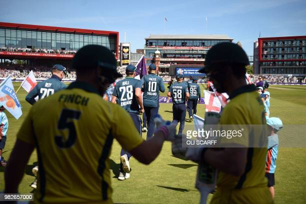 England players take to the pitch as Australia's Aaron Finch and Travis Head touch gloves at the start of the fifth One Day International cricket...