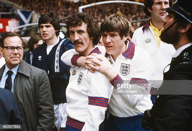 England players Terry McDermott and Emlyn Hughes share a hug as Alan Hansen of Scotland looks on before a Home International match between England...