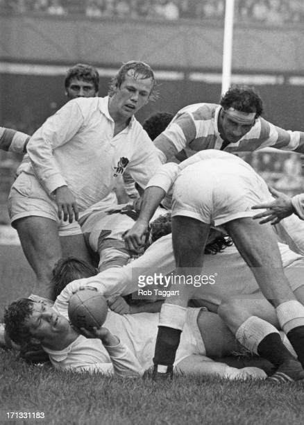 England prop Fran Cotton on the ground with the ball and England hooker Peter Wheeler above him in a maul during a match against Argentina at...