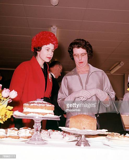 England Queen Elizabeth II is pictured judging a cake competition during a visit to Slough
