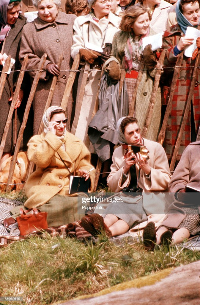 England. 1957. Queen Elizabeth II is pictured taking cine films at the Badminton Horse Trials as she sits with Princess Margaret (left). : News Photo