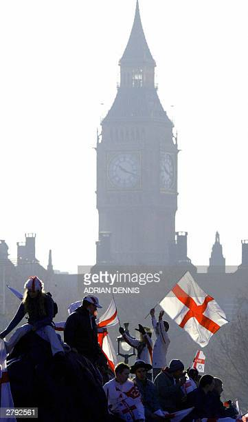 England rugby fans wave English flag as they celebrate their team's World Championship win with Big Ben behind them at Trafalgar Square, in London 08...