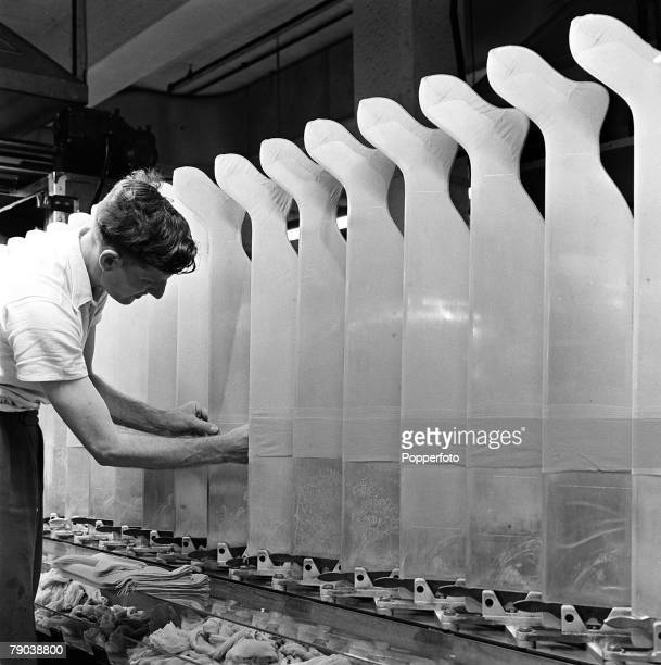 England Scenes from a nylon stocking factory as a male operative pulls them over moulds
