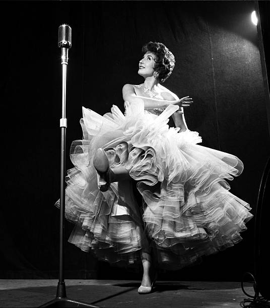 """England. 1954. Singer and entertainer Alma Cogan is pictured performing in the BBC Midland Home Service show """"Music Comes to Town""""."""