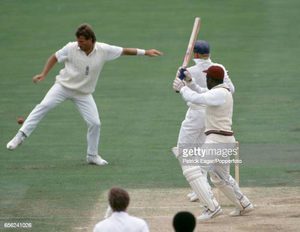 England slip fielder Ian Botham attempts to stop a shot from West Indies batsman Viv Richards with his foot during the 5th Test match between England...