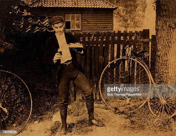 England Social History Albumen print of young man who pours a bottle of beer into a glass as his penny farthing bicycle leans against a fence circa...