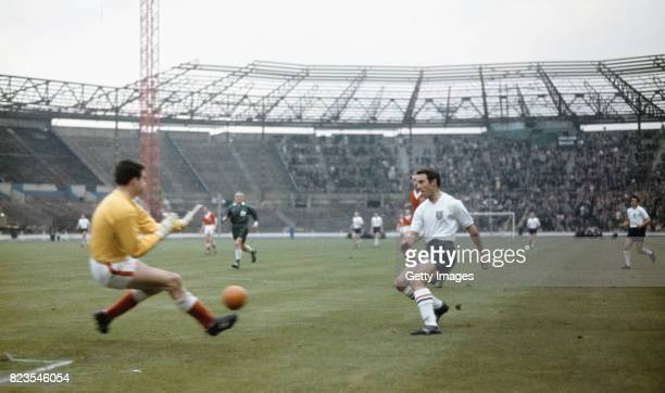 England striker Jimmy Greaves shoots at goal at Wales goalkeeper Tony Millington during the Home International Championship match between England and...