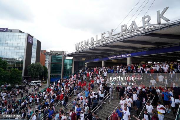 England supporters exit Wembley Park Station as they arrive ahead of the UEFA EURO 2020 final football match between England and Italy in northwest...