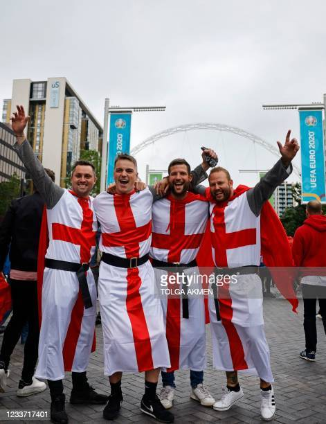 England supporters in fancy dress, pose for a photograph on Olympic Way as they arrive at Wembley Stadium ahead of the UEFA Euro 2020 European...