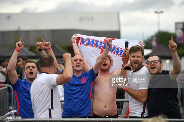 England supporters pose for a photograph as they prepare to cheer on their team at the 4TheFans Fan Park in Manchester while watching the UEFA EURO...