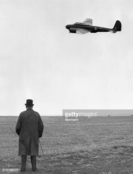 7/23/1941 England The well known figure of Prime Minister Winston Churchill easily recognizable even though from the rear watches a flying fortress...