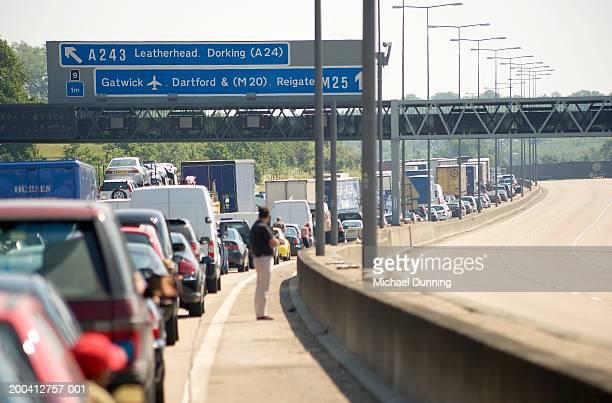 England, traffic jam on M25 motorway, man waiting outside car