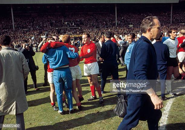 England trainer Les Cocker is hugged by Nobby Stiles and Alan Ball watched by George Cohen during the celebrations after the FIFA World Cup Final...