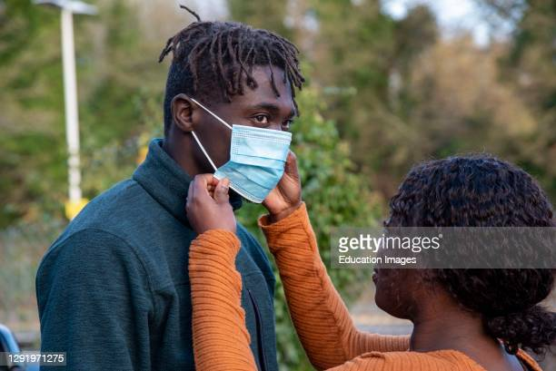 England, UK, A couple with the woman adjusting her husbands facemask during Covid-19 outbreak.