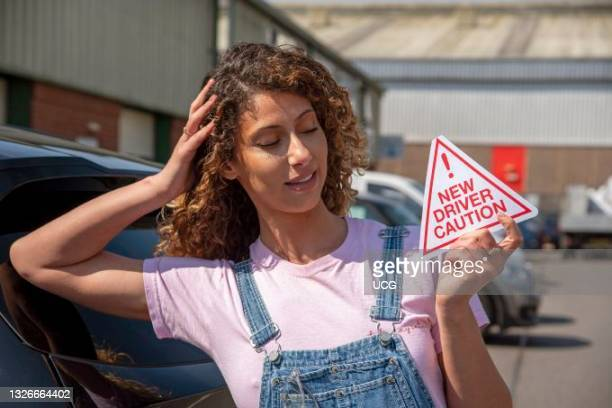 England, UK, New driver, young attractive woman holding a new driver caution sign to display on her car after passing the driving test.
