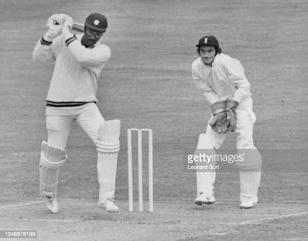England wicketkeeper Alan Knott looks on from behind the stumps as batsman Clive Lloyd of the West Indies cricket team plays a drive off a delivery...