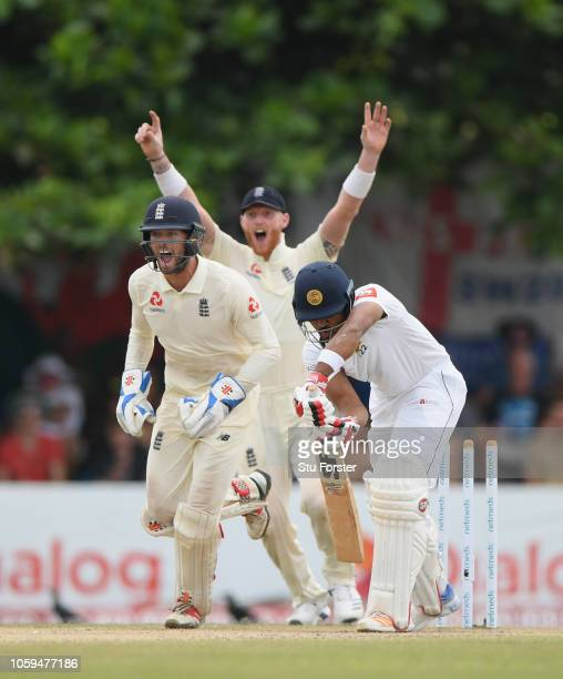 England wicketkeeper Ben Foakes and slip Ben Stokes celebrate as Sri Lanka batsman Dinesh Chandimal is bowled by Jack Leach during Day Four of the...