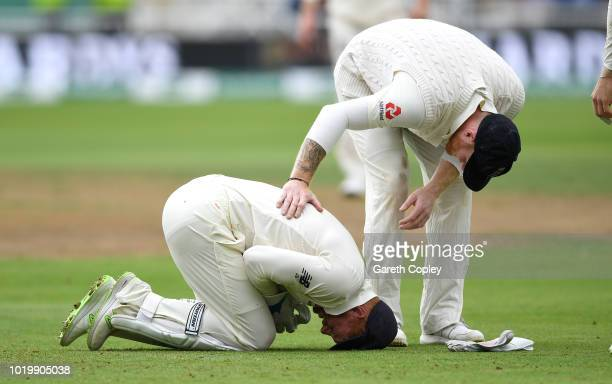 England wicketkeeper Jonathan Bairstow lies on the ground after injuring his finger as Ben Stokes checks on his during day three of the Specsavers...