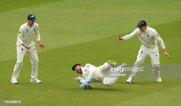 England wicketkeeper Jonny Bairstow celebrates with Joe Root and Jason Roy after catching William Porterfield during day three of the Specsavers Test...