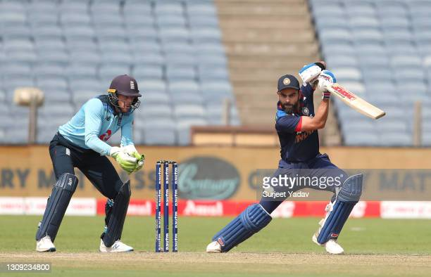 England wicketkeeper Jos Buttler looks on as India batsman Virat Kohli cuts a ball for some runs during the 2nd One Day International between India...