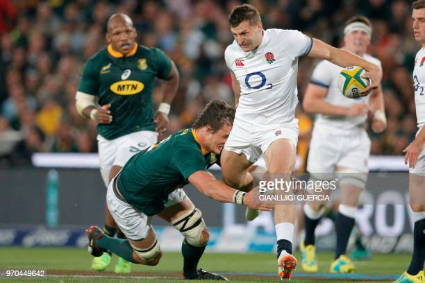 England winger Jonny May is tackled by South Africa lock Franco Mostert during the rugby union test match between South Africa and England at Ellis...