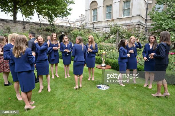 England women's cricket team captain Heather Knight stands with teammates as they stand near the ICC Women's World Cup Cricket trophy during a...