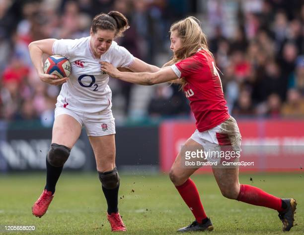 England Women's Emily Scarratt evades the tackle of Wales Women's Hannah Jones during the Women's Six Nations match between England Women and Wales...