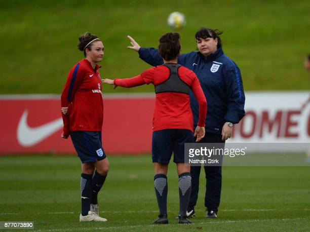 England Women's interim head coach Mo Marley talks to Jodie Taylor and Fara Williams during a training session at St Georges Park on November 21 2017...