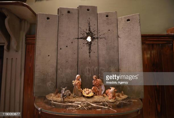 Englandbased street artist Banksy's artwork named Scar of Bethlehem depicting nativity scene with Mary and Joseph and the baby Jesus in front of a...