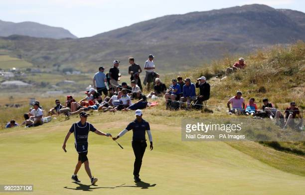 England's Aaron rai is handed a club by his caddy on the fourteenth green during day one of the Dubai Duty Free Irish Open at Ballyliffin Golf Club