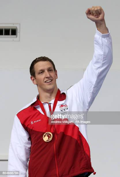 England's Adam Brown celebrates as he collects his gold medal for the Men's 4 x 100m Medley Relay Final at Tollcross International Swimming Centre...