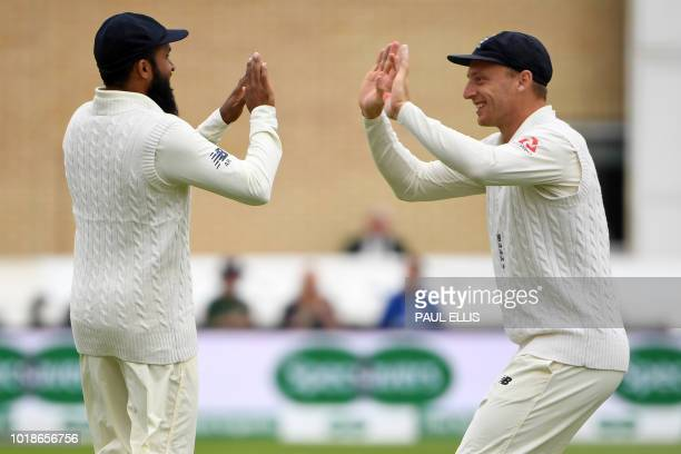 England's Adil Rashid celebrates with England's Jos Buttler after catching out India's Cheteshwar Pujara during play on the first day of the third...