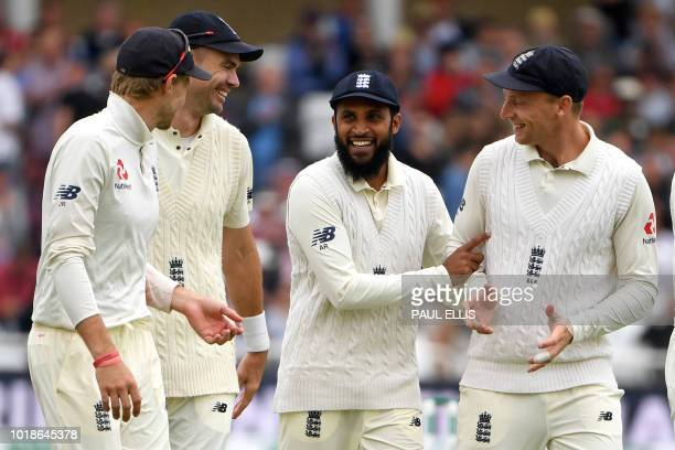 England's Adil Rashid smiles as he celebrates catching out India's Cheteshwar Pujara during play on the first day of the third Test cricket match...