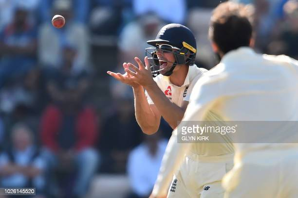 England's Alastair Cook catches India's captain Virat Kohli during play on the fourth day of the fourth Test cricket match between England and India...