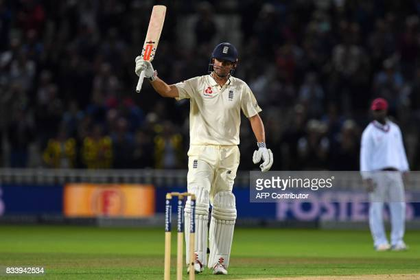 England's Alastair Cook celebrates reaching 150 under lights on the first day of the first Test cricket match between England and the West Indies at...