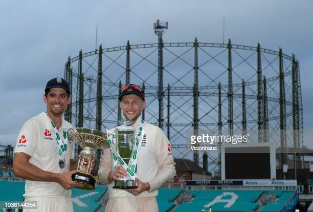 England's Alastair Cook holds the Pataudi Trophy and Joe Root the Specsavers Trophy after the series win over India during the 5th Specsavers Test...