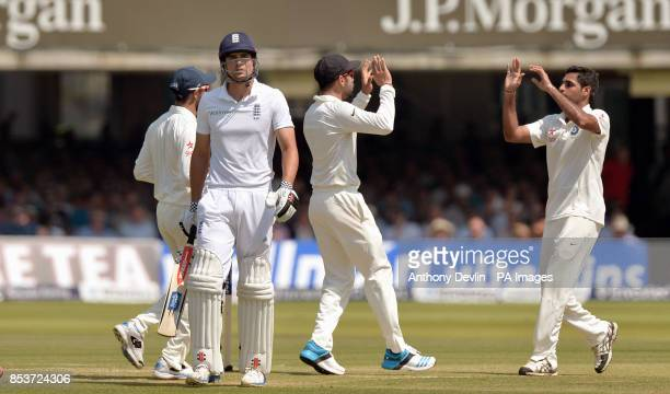 England's Alastair Cook leaves the field after being caught behind by India's MS Dhoni off the bowling of Bhuvneshwar Kumar for 10 during day two of...