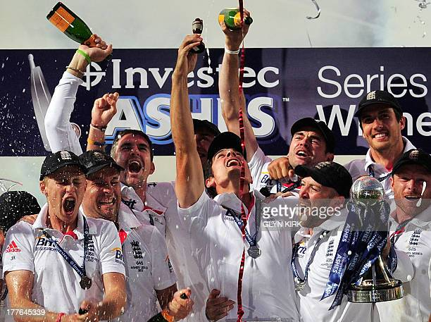 England's Alastair Cook lifts a replica of the Ashes Urn amid his team mates as they celebrate their series win after drawing on the final day of the...