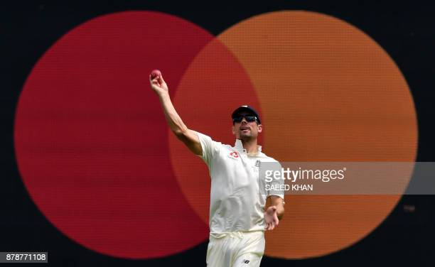 England's Alastair Cook returns a ball to bowler Chris Woakes on the third day of the first cricket Ashes Test between England and Australia in...