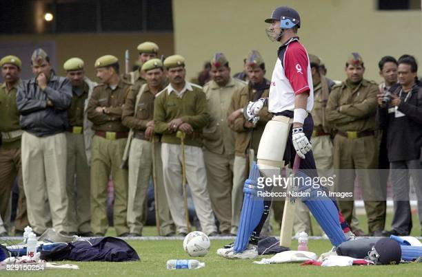 England's Andrew Caddick is watched by police officers at the Green Park cricket ground Kanpur India