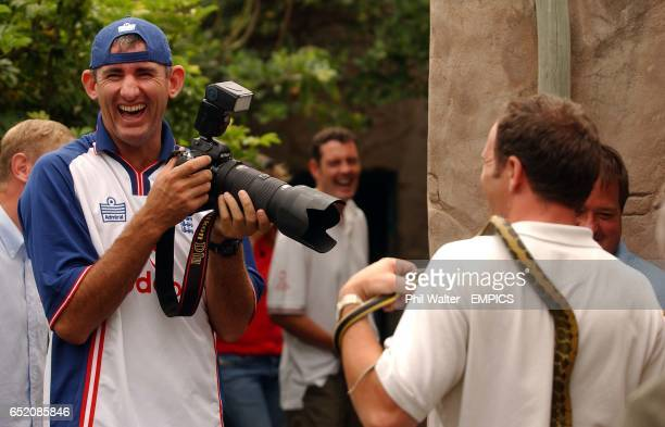 England's Andrew Caddick photographs a photographer holding a Taiwanese Rat Snake at the Fitzsimons Snake Pit in Durban