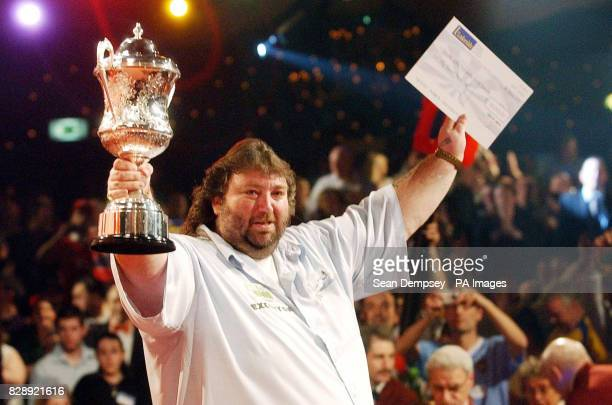 England's Andy Fordham celebrates with the winners cheque and trophy after winning the Final of the Lakeside World Professional Darts Championships...