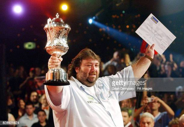 England's Andy Fordham shows his emotions as he celebrates with the winners cheque and trophy after winning the Final of the Lakeside World...