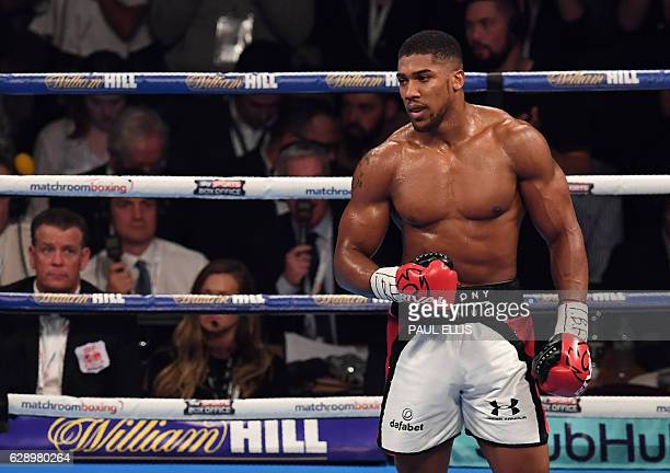 England's Anthony Joshua clebrates beating USA's Eric Molina during the IBF World Heavyweight Championship boxing match in Manchester northwest...