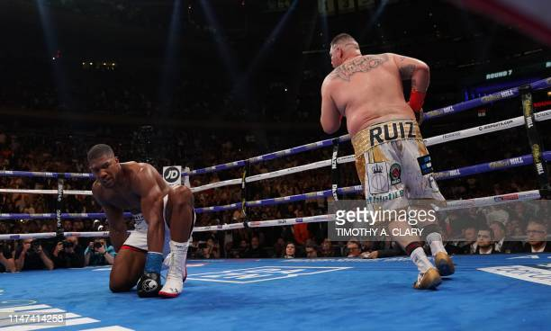 TOPSHOT England's Anthony Joshua kneels after being knocked down by USA's Andy Ruiz in the 7th round to win by TKO during their 12round IBF WBA WBO...